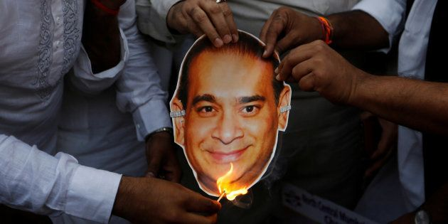 Activists of the youth wing of India's main opposition Congress party burn a cut-out with an image of...