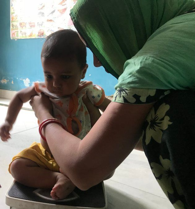 A toddler being weighed at an Anganwadi centre in