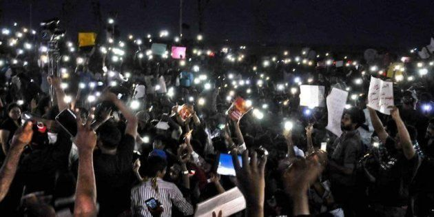 Hundreds of protestors at Chennai's Marina beach hold up their mobile phones while protesting against...