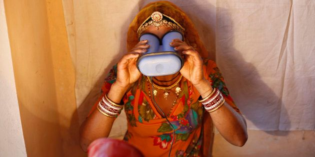 A woman goes through the biometric data collection process to get an Aadhaar
