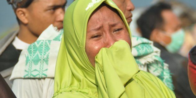 A woman cries as people look at the damages after an earthquake and a tsunami hit Palu, on Sulawesi island...
