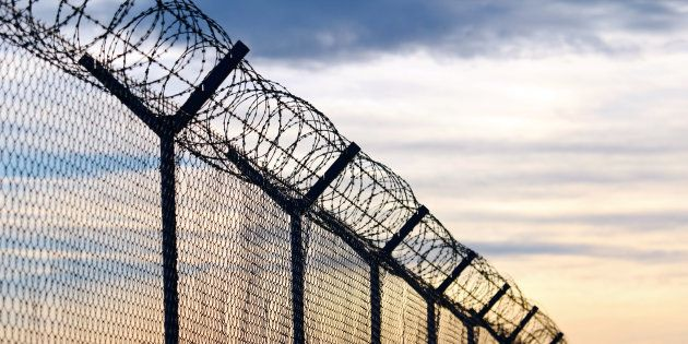 Silhouette of Barbed Wire fence against a Cloudy