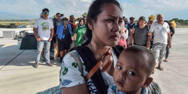 People affected by the earthquake and tsunami wait to be evacuated on an air force plane in Palu, Central...