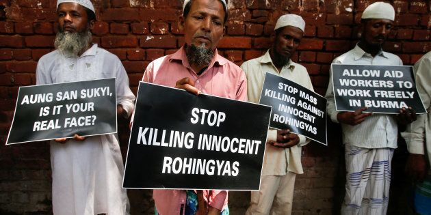 Rohingya Muslim refugees hold placards during a protest rally against what the protesters say are killings...
