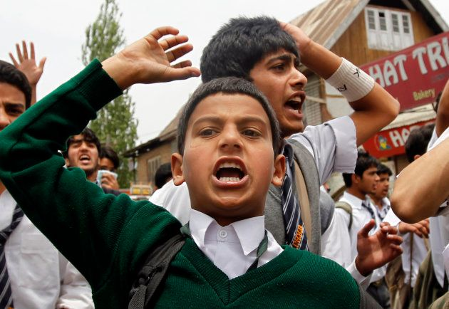 Kashmiri school children shout slogans against Indian security forces during a protest over the killing...
