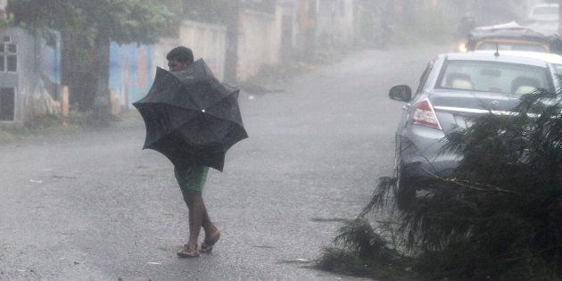 A man tries to hold his umbrella during strong winds and rain caused by Cyclone Titli, near Gopalpur...