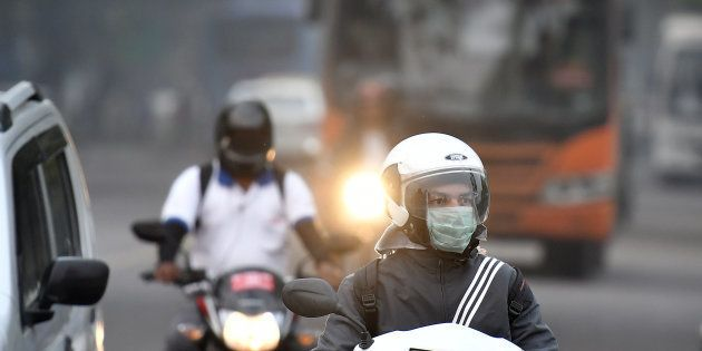 A motorcyclist wearing a face mask drives along a road in New