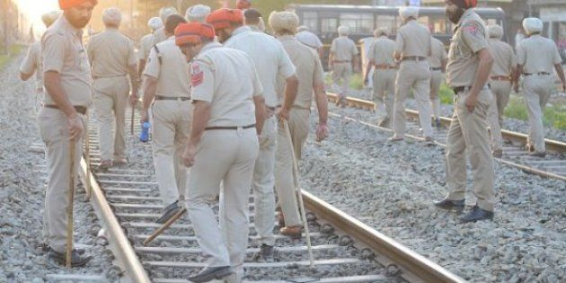 Indian Punjab Police personnel walk at the scene of the accident along railroad tracks in Amritsar on...