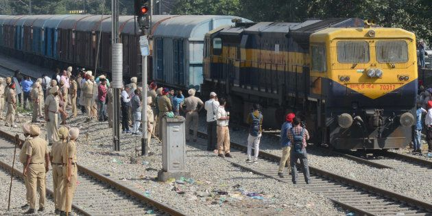Police stand guard as a freight train passes along rail tracks towards Amritsar railway station, two...