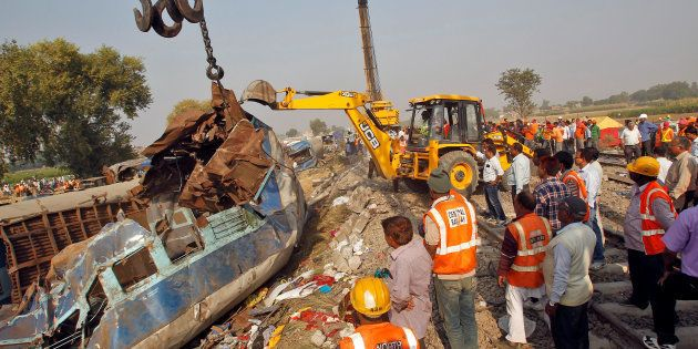 Rescue workers move a carriage at the site of a train derailment in Pukhrayan, south of Kanpur city,...