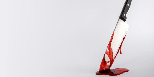Kitchen knife dripping in blood on light background with copy
