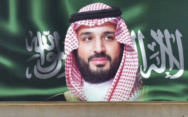 A picture taken on October 22, 2018 shows a man walking past a portrait of Saudi Crown Prince Mohammed...