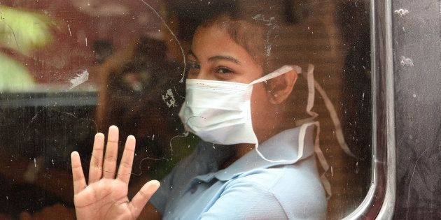 A girl covers her face with a mask to protect herself from the pollution at Laxmi Nagar on October 23,...