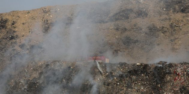 A firefighter tries to douse fire as smoke billows from the burning garbage at the Bhalswa landfill site...