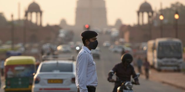 A traffic cop in Delhi wears a mask to protect himself from the