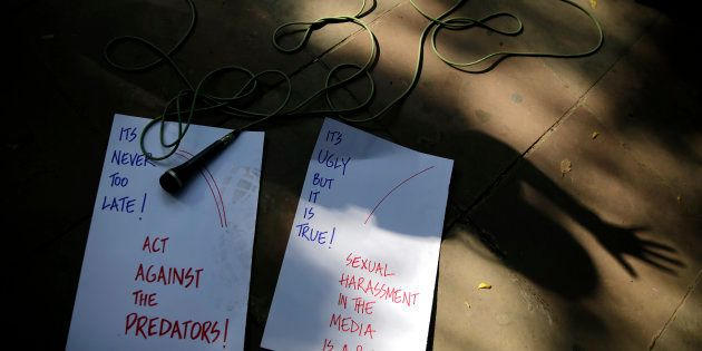 Placards and a microphone are seen lying on the sidewalks as Indian journalists protest against sexual...