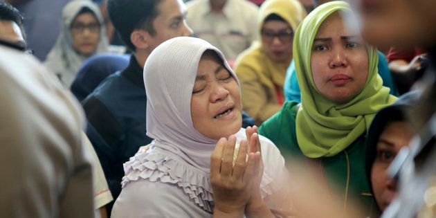 A relative of passengers prays as she and others wait for news on a Lion Air plane that crashed off Java...
