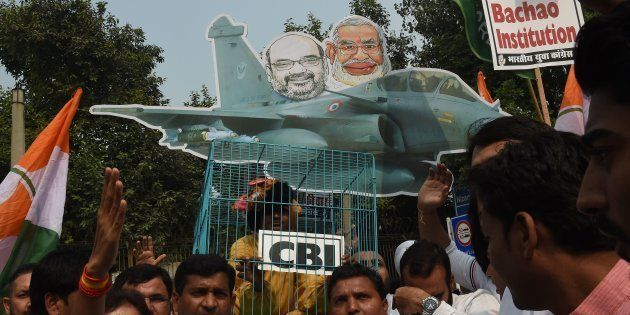 Supporters and members of the Congress party take part in a protest featuring an image of Prime Minister...