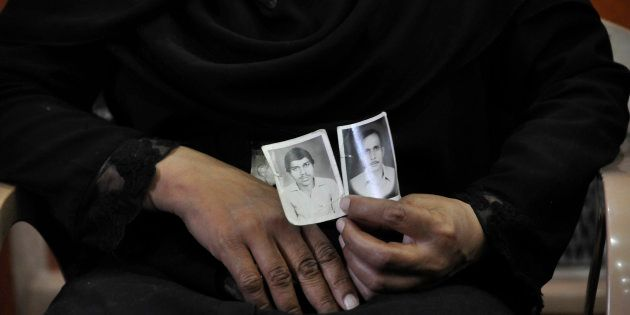 A woman shows picture of her relatives who were killed in the Hashimpura massacre in