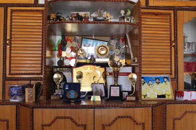 A growing collection of trophies, medals, and photos crowd the shelves of a cabinet in the living room...
