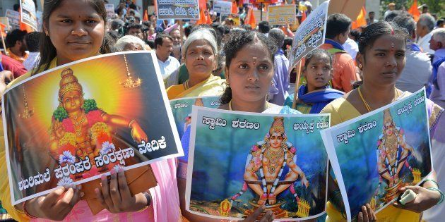 Devotees of Ayyappa hold posters of the deity at a rally in Bangalore on October 27,