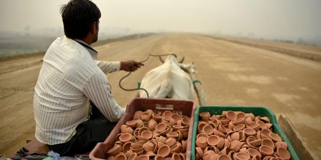 A man selling traditional earthen lamps ahead of Diwali festival, rides a bullock cart through an under...