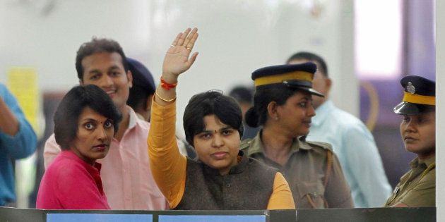 Trupti Desai, a women's rights activist, waves from inside the Cochin International Airport at Kochi,...