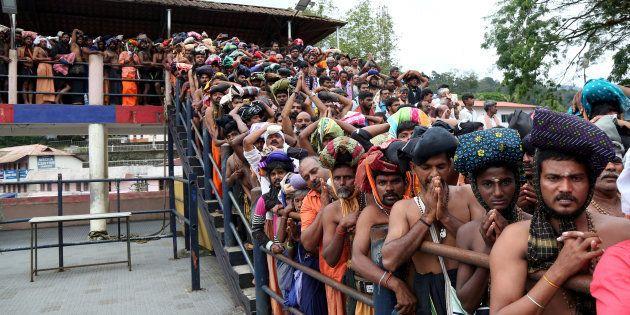 Hindu devotees wait in queues inside the premises of the Sabarimala