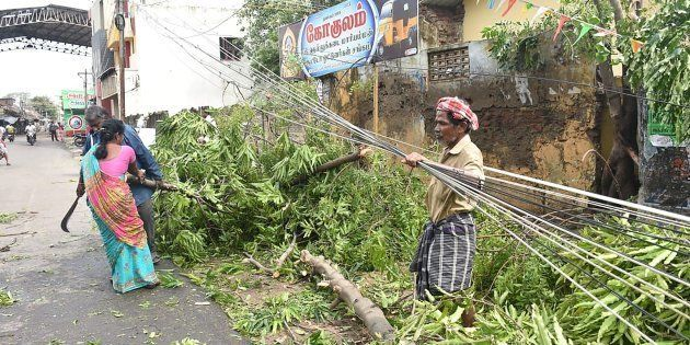 Residents clear away fallen trees near the train station in Nagapattinam in India's southern Tamil Nadu...