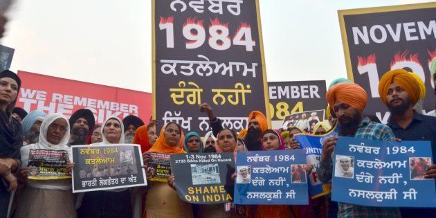 Activists participate in a candle march demanding justice for those who were killed in the 1984 anti-Sikh