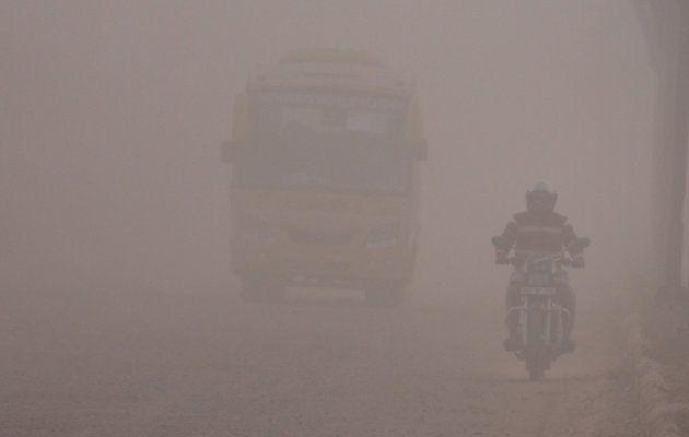Commuters on a dusty road in Gurugram.
