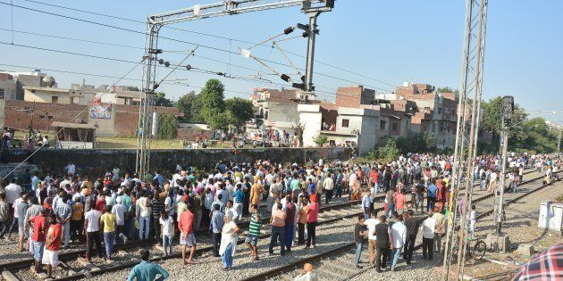 Punjab Police personnel and local people at the scene of the accident along train tracks.