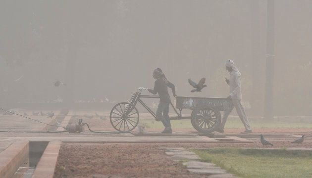 NEW DELHI, INDIA - NOVEMBER 20: Labourers work early in the morning amid heavy smog at Humayun's Tomb...