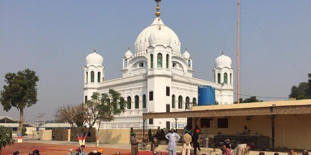 Sikh pilgrims sit in front of Kartarpur Gurdwara Sahib before the groundbreaking