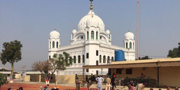 Sikh pilgrims sit in front of Kartarpur Gurdwara Sahib before the groundbreaking