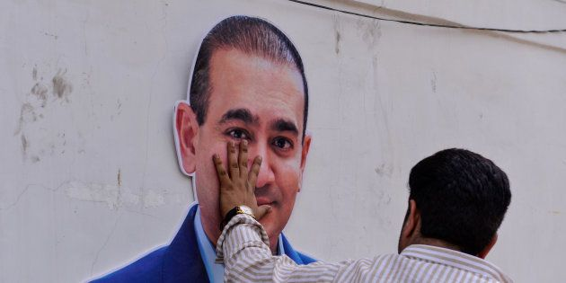 An Indian supporters of the Congress Party keeps his hand on the face of a cut out of billionaire jeweller...