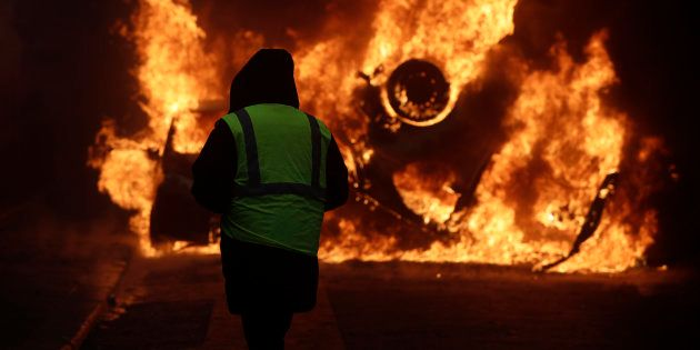 A demonstrator watches a burning car near the Champs-Elysees avenue during a demonstration Saturday,...