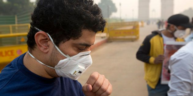 A man coughs even after wearing a mask a day after Diwali festival in New