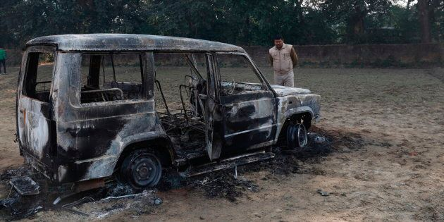 A police officer inspects the vandalised remains of a car in which Inspector Subodh Kumar Singh was