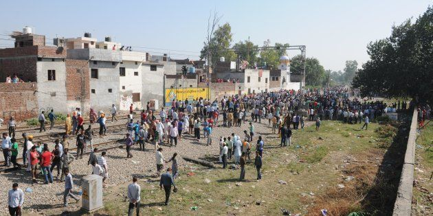 Punjab Police personnel and local people gather at the scene of the