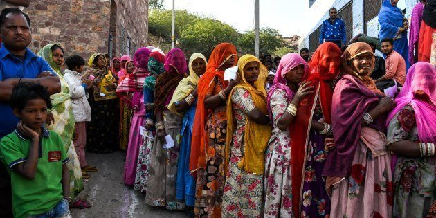 Women stand in queue to cast their vote at a local polling station on 7