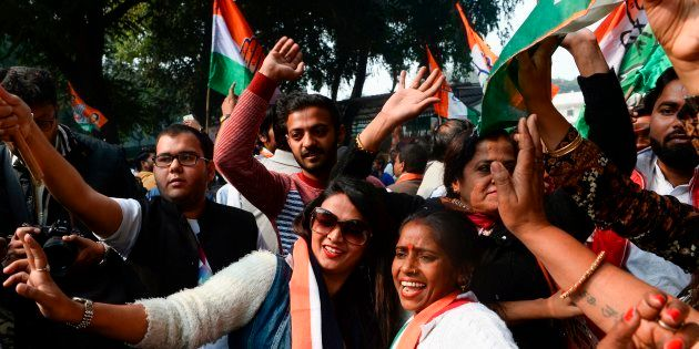 Congress supporters celebrate outside the party headquarters in New