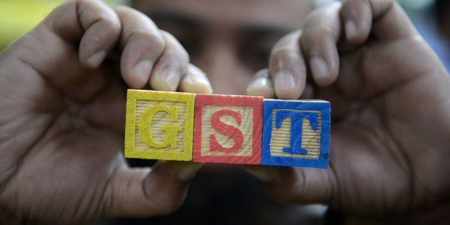 An Indian consumer goods trader shows letters GST representing 'Goods and Services Tax' (GST) at his...