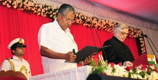 Incoming Chief Minister of Kerala Pinarayi Vijayan (C) stands alongside Governor of Kerala P. Sathasivam(R)...