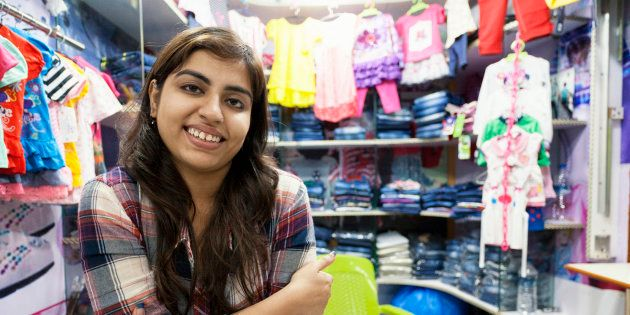 Young Indian woman selling clothes at a small store in a shopping mall in Delhi,