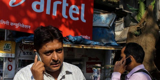 Pedestrians talk on their mobile phones in front of a store displaying a Bharti Airtel Ltd. advertisement...
