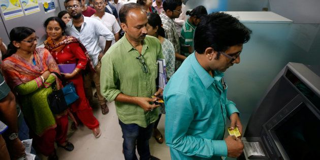 People wait to withdraw and deposit their money at an ATM kiosk in Kolkata, India, November 8,