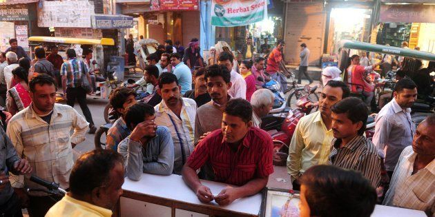 Indian residents exchange 500INR notes for coins at a roadside money changer, who charges 100INR per...