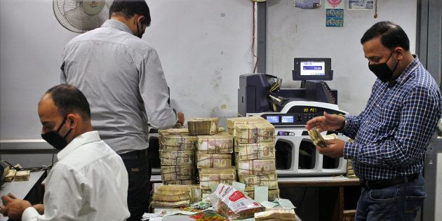Bank employees count old ₹500 banknotes inside a