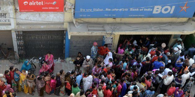 People queue outside a bank as they wait to deposit and exchange ₹500 and ₹1,000 notes in Amritsar on...